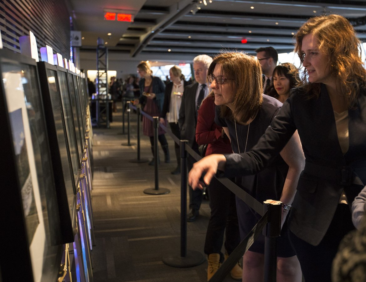 Bank of Canada employees examine the winning entries of the photo calendar  contest at the Governor's holiday reception